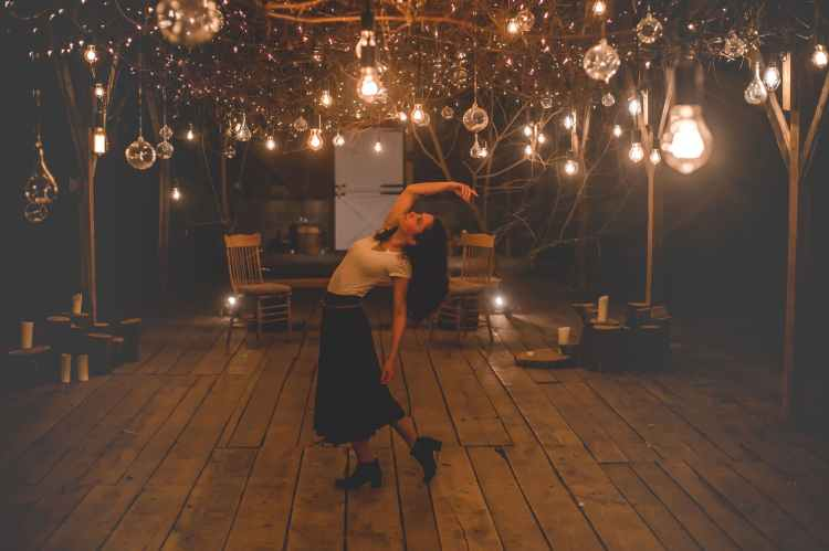 woman dancing on terrace with lights turned on
